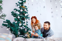 Christmas happy family of three persons decorating fir tree with gift boxes over white bedroom background Royalty Free Stock Image