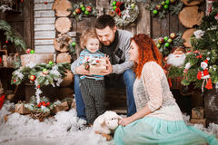 Christmas happy family of three persons and fir tree with gift boxes new year winter decorated background Stock Photography