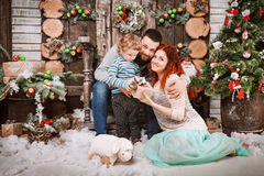 Christmas happy family of three persons and fir tree with gift boxes new year winter decorated background Stock Image