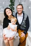 Christmas happy family of three persons sitting on the bed of white bedroom background royalty free stock photography