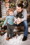 Happy father gives a Christmas gift to his son in decorations with fir tree with gift boxes and wooden background. Christmas happy family of two persons happy royalty free stock image