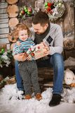Happy father gives a Christmas gift to his son in decorations with fir tree with gift boxes and wooden background. Christmas happy family of two persons happy royalty free stock photography