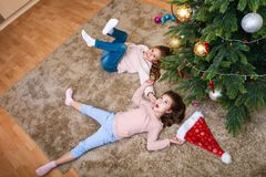 Christmas happy funny children sisters lying under the christmas tree and having fun royalty free stock photo