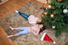 Christmas happy funny children sisters lying under the christmas tree and having fun royalty free stock photography