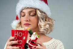 Christmas and New Year.  Woman in santa`s hat is holding a cup of coffee. Stock Photo