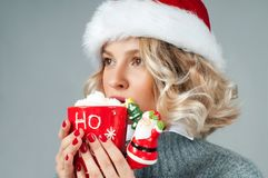 Christmas and New Year.  Woman in santa`s hat is holding a cup of coffee. Stock Photos