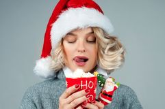 Christmas and New Year.  Woman in santa`s hat is holding a cup of coffee. Royalty Free Stock Image