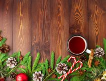 Christmas and Happy New Year background with tea. Top view, copy space. Fir branches, brown dark wooden table. Christmas and Happy New Year background with tea Royalty Free Stock Photo