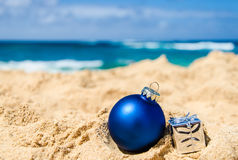 Christmas and Happy New Year background on the tropical beach. Merry Christmas and Happy New Year background with gift and ball on the tropical beach near ocean stock photo