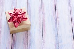 Christmas and happy new year brown gift box and red ribbon with. Tag on wood background. Top view with space for use Stock Images