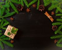Christmas and Happy New Year dark brown background. Gift Christmas box, fir branches, top view, copy space. Christmas and the Happy New Year dark brown Stock Photo