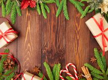 Christmas and Happy New Year dark brown background. Gift Christmas box, fir branches, wooden table, top view, copy space. Christmas and Happy New Year dark brown Stock Photos
