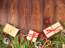 Christmas and Happy New Year dark brown background. Gift Christmas box, fir branches, wooden table, top view, copy space. Christmas and Happy New Year dark brown Stock Images
