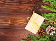 Christmas and Happy New Year dark brown background. Gift Christmas box, fir branches, wooden table, top view, copy space. Christmas and Happy New Year dark brown Royalty Free Stock Images