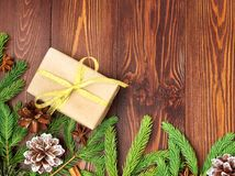 Christmas and Happy New Year dark brown background. Gift Christmas box, fir branches, wooden table, top view, copy space. Christmas and Happy New Year dark brown Stock Image