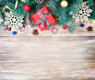 Christmas or Happy New Year decoration background. Composition f. Rom sparkling christmas tree branches with a red gift box and xmas balls on a rustic wooden royalty free stock photo