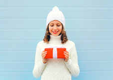 Christmas happy smiling young woman holds gift box in hands wearing a knitted hat sweater over blue Stock Images