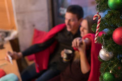 Christmas Happy young couple using smart phone sitting at home. Royalty Free Stock Image
