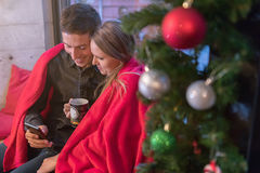 Christmas Happy young couple using smart phone sitting at home. Stock Photo