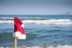 Christmas hat against blue sea Stock Photos