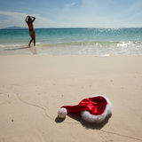 Christmas hat on beach. Closeup christmas hat on a white stropical sandy sea beach ans woman in bikini Stock Photo