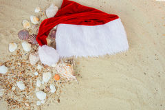 Christmas hat on the beach. Santa   the sand near shells. Holiday. New year vacation. Copy space. Frame. Top view. Royalty Free Stock Image