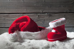 Christmas hat and boot on heap of snow against wooden background royalty free stock image