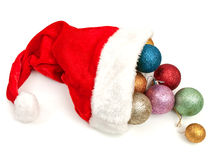 Christmas hat with Christmas balls. Red christmas hat with new-year yoys over white background Royalty Free Stock Photography