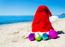 Christmas hat with christmas balls on the beach Stock Photo