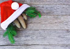 Christmas hat with Christmas tree branches and cones. Santa cap. And fir-tree branch with cones on rustic wood. Christmas concept in horizontal layout stock images