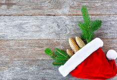 Christmas hat with Christmas tree branches and cones. Santa cap. And fir-tree branch with cones on rustic wood. Christmas concept in horizontal layout stock photo