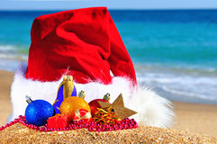 Christmas hat with colored baubles on the seashore Royalty Free Stock Images