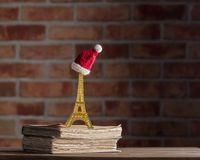 Christmas hat on Eiffel tower souvenir and old books. On wooden table at brick wall background. Library royalty free stock images