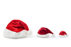 Christmas hat family. Three santa hat of different sizes in a row on white background Royalty Free Stock Photos