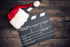 Christmas hat with film board cutout. On wooden table Royalty Free Stock Photos