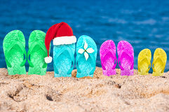 Christmas hat on flip flops in the sand of a beach Stock Images