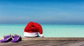 Christmas hat and flip flops on wooden jetty Stock Images