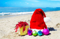 Christmas hat with gift box and christmas balls on the beach Stock Photos