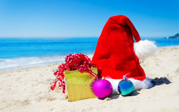 Christmas hat with gift box and christmas balls on the beach Stock Photo
