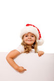 Christmas hat girl pointing to white banner. Smiling happy christmas hat girl pointing to white banner - isolated Stock Images