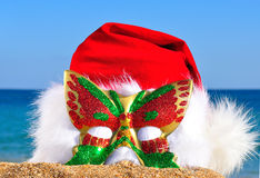 Christmas hat with glittering carnival mask on the seashore Stock Image