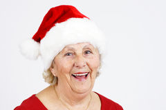 Christmas hat grandma smiling. Grand-mother or elderly woman with big happy smile wearing Santa Claus hat; perfect for Christmas and seniors themes Stock Photo
