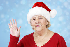 Christmas hat grandma waving over blue Royalty Free Stock Photos