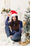 Christmas hat. Happy young woman celebrating Christmas at home Royalty Free Stock Images