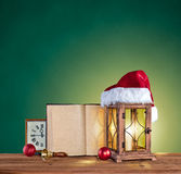 Christmas hat, lantern, book and clock on a green backgr Royalty Free Stock Image