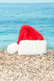 Christmas hat lies on the beach. Royalty Free Stock Images