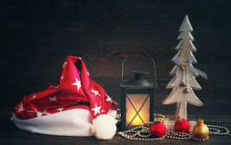 Free Christmas Hat Of Santa, Christmas Lamp And Glass Spheres  With A Wooden Decorative New Year Tree On A Wooden Background Royalty Free Stock Photos - 81721858