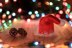 Christmas hat and pine cone on a background garlands.  Royalty Free Stock Photography