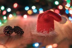Christmas hat and pine cone on a background garlands. Christmas hat and pine cones lie on a wooden table against a garland Royalty Free Stock Image