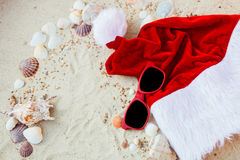 Christmas hat and red sunglasses on the beach. Santa   eyeglasses  the sand near shells. Holiday. New year vacation. Copy space. F Stock Image